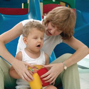 Menino de aproximadamente, 2 anos, cabelos claros e lisos, sentado, com Chocalhos Gruda-gruda vermelho e amarelo nas mãos, com a mediação da mãe, que está posicionada atrás dele.