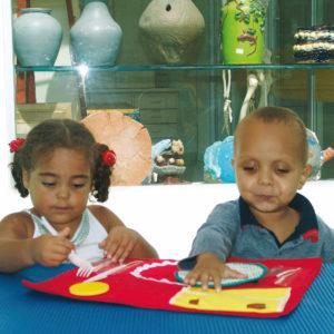 Um menino e uma menina de aproximadamente 5 anos, estão sentadas e à sua frente, a toalha do brinquedo 1...2...Feijão com Arroz diante do brinquedo. À esquerda a menina segura a colher branca e à direita, o menino toca o envelope de tecido.