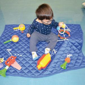 Menino de aproximadamente 1 ano, cabelos escuros, lisos e curtos. Usa óculos. Está sentado sob o Painel ao Pé do Ouvido e com a mão esquerda explora o chocalho colorido. Ao seu redor, sob o Painel, os brinquedos sonoros.