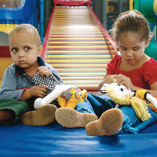 Um menino e uma menina de aproximadamente 3 anos. Estão sentados sob um colchonete e têm nas mãos o Casal Legal Leo e Lu. Ao fundo, o escorregador do Laraparque.