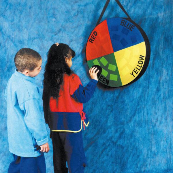 Um menino e uma menina estão em pé, em frente ao painel do Bug-Ball. Ela tem na mão direita, uma bolinha preta, que aproxima do velcro verde do painel.