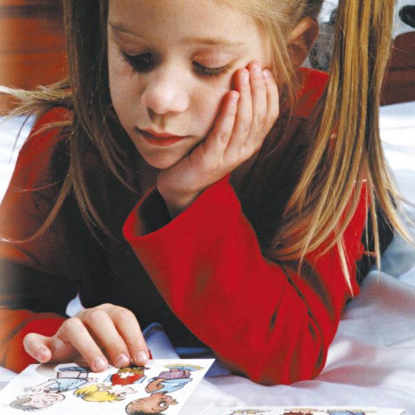 Deitada de barriga para baixo, uma menina, apoiando a mão esquerda no queixo, toca uma figura do livro com a mão direita.
