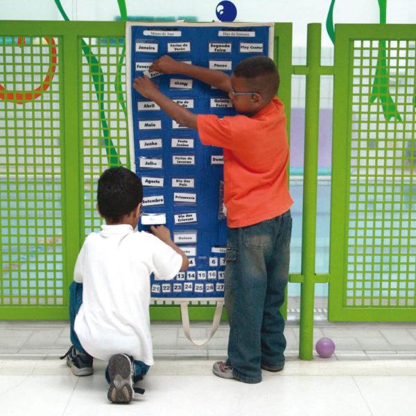 Dois meninos estão de costas, em frente ao painel do Passatempo. O da esquerda, está agachado e toca um dos cartões, enquanto o que está à direita, em pé, está com ambas as mãos em um dos cartões.