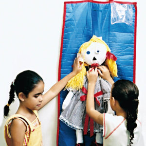 Duas meninas de aproximadamente 6 anos, em pé, em frente ao tapete retangular. A menina à esquerda, toca o cabelo da boneca de pano, enquanto a da direita, toca o laço vermelho da gola do vestido.