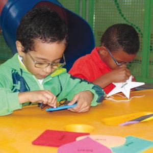 Dois meninos de aproximadamente 4 anos e óculos estão sentados em frente à uma mesa amarela. À frente deles, as placas do brinquedo Tack. À esquerda, o menino segura uma placa azul e, ao seu lado, um menino segura uma estrela branca.