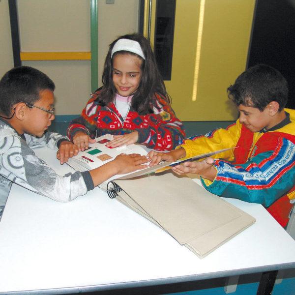 Dois meninos e uma menina sentados em frente à uma mesa branca, tocam páginas do Livro Sensorial.