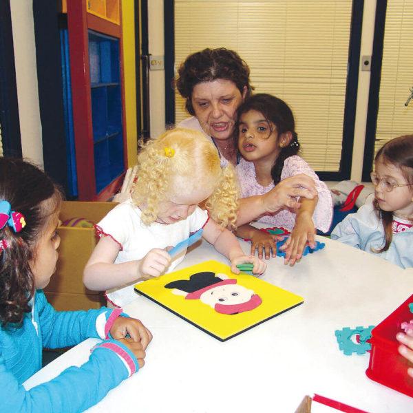 Três meninas de aproximadamente 5 anos, sentadas lado a lado, em frente à uma mesa branca. A que está no meio, cabelos claros e cacheados, tem nas mãos, peças de encaixe do brinquedo Toninho.