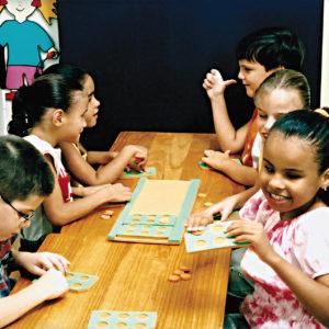 Seis crianças de aproximadamente 6 anos, sentadas em frente à uma mesa retangular, sendo um menino e duas meninas à esquerda e duas meninas e um menino à direita. Em cima da mesa, os retângulos e celas que compõem o brinquedo Alphabraile.