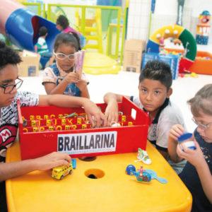 Dois meninos e uma menina de aproximadamente 6 anos, estão sentados em frente à uma mesa, onde está o brinquedo Brailarina. Os meninos à esquerda e à direita, estão com as mãos dentro de uma das divisórias, enquanto a menina ao centro, segura um objeto com ambas as mãos.