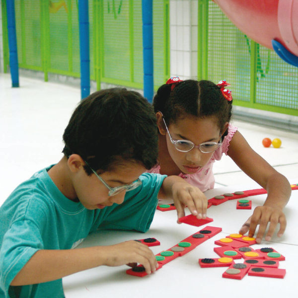 Um menino e uma menina de aproximadamente 5 anos, sentados lado a lado. Tocam peças do Dominó de Texturas.