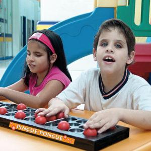 Uma menina e um menino de aproximadamente 6 anos, sentados lado a lado, tocam nas bolinhas de pingue-pongue, encaixadas na placa do brinquedo Pingue-Pongue.